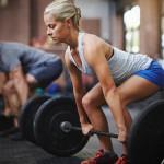 Personal trainers and client perform successful deadlift