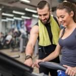 Personal trainer helping client with treadmill, increasing personal training sales