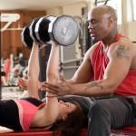 Personal trainer helps client with dumbbell bench press