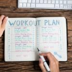 Personal trainers writing and pricing flagship program in notebook